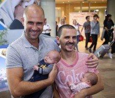 Amir Ohana (à gauche) et son partenaire vu à l'aéroport international Ben Gourion de retour des États-Unis avec leurs bébés, le 26 septembre 2015. (Crédit : Flash90)